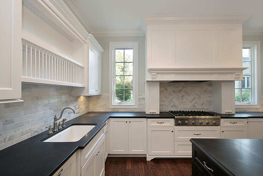 black granite counter with white cabinets and a stove